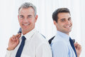 Smiling businessmen posing back to back together while holding t in bright office their jacket Royalty Free Stock Images