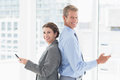 Smiling businesswoman back to back with colleague in an office Stock Photo