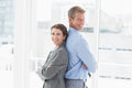 Smiling businesswoman back to back with colleague in an office Royalty Free Stock Photo