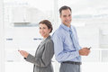 Smiling businesswoman back to back with colleague in an office Stock Images