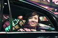 Smiling businesswoman with car window rolled down looking out at the nightlife in beijing Stock Photography