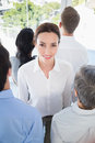Smiling businesswoman with colleagues back to camera in the office Royalty Free Stock Photos