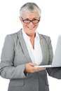 Smiling businesswoman with glasses holding her laptop on white background Stock Image
