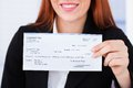 Smiling businesswoman holding cheque Royalty Free Stock Photo