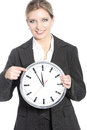 Smiling businesswoman holding a clock attractive young and pointing to the time of five minutes to twelve isolated on white Stock Photos