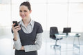 Smiling businesswoman holding her smartphone posing in bright office Royalty Free Stock Image