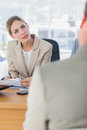 Smiling businesswoman looking at interviewee in the office Royalty Free Stock Image