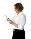 Smiling businesswoman looking at tablet pc Royalty Free Stock Images