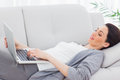 Smiling businesswoman lying on sofa using laptop at office Stock Photo