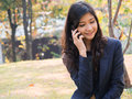 Smiling businesswoman making a phone call in the garden Royalty Free Stock Image