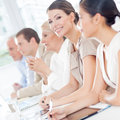 Smiling businesswoman in a meeting sitting with her colleagues Royalty Free Stock Image