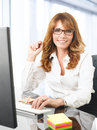 Smiling businesswoman at office desk with a computer portrait of mature Royalty Free Stock Photography