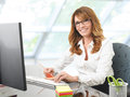 Smiling businesswoman at office desk with a computer portrait of mature Royalty Free Stock Photo