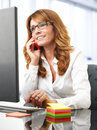 Smiling businesswoman on the phone in office portrait of a mature at desk with a computer Royalty Free Stock Photos