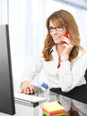 Smiling businesswoman on the phone in office portrait of a mature at desk with a computer Royalty Free Stock Photo
