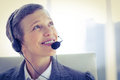 Smiling businesswoman phoning with headphone at the office Stock Photography