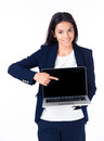 Smiling businesswoman pointing on the blank laptop screen finger over white background and looking at camera Stock Image