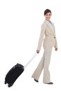 Smiling businesswoman pulling suitcase against white background Stock Photography