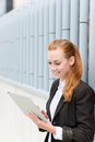 Smiling businesswoman reading tablet pc young digital against the wall Royalty Free Stock Images