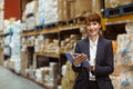 Smiling businesswoman scrolling on digital tablet in a large warehouse Stock Image