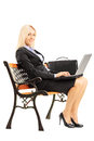 Smiling businesswoman sitting on a bench and working on a laptop young wooden isolated white background Royalty Free Stock Photos