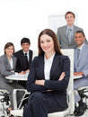 Smiling businesswoman sitting in front of her team Stock Photos
