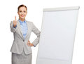 Smiling businesswoman standing next to flip board Stock Images