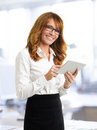 Smiling businesswoman with tablet in office digital Stock Photos