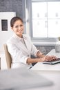 Smiling businesswoman typing on keyboard portrait of happily sitting at office desk Royalty Free Stock Photos