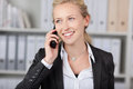 Smiling businesswoman using mobile phone happy young in office Stock Image