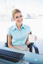 Smiling businesswoman wearing glasses holding coffee in bright office Royalty Free Stock Images