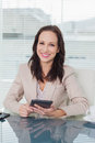 Smiling businesswoman working on her tablet pc in bright office Royalty Free Stock Photography