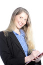 Smiling businesswoman writing notes with long blonde hair standing on a handheld clipboard Stock Photos