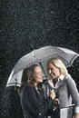 Smiling businesswomen under one umbrella in rain two happy standing an together Royalty Free Stock Image