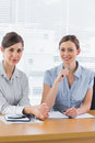 Smiling businesswomen working together and looking at camera desk in office Royalty Free Stock Images