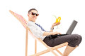 Smiling busy man with laptop sitting on a beach chair and holdin holding cocktail isolated white background Royalty Free Stock Image
