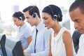 Smiling call center employees sitting in line with their headset Stock Photo
