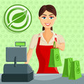 Smiling cashier girl at eco green store supermarket handing out bag Royalty Free Stock Photo