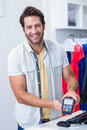 Smiling cashier showing credit card reader portrait of in clothing store Stock Images