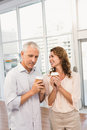 Smiling casual business colleagues having coffee together in the office Royalty Free Stock Photos