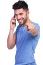 Smiling casual man pointing his finger on the phone to camera while talking Royalty Free Stock Images