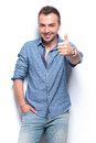 Smiling casual man shows thumb up young the gesture and smiles with a hand in pocket on white background Royalty Free Stock Image