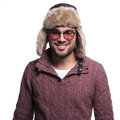 Smiling casual man in winter clothes and furry hat isolated on white background Stock Photos