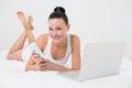 Ležérní žena mobil a přenosný počítač v postel