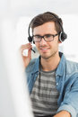 Smiling casual young man with headset using computer Royalty Free Stock Photo