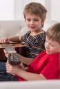 Smiling caucasian boy playing acoustic guitar boys sitting on couch and adjusting strings Royalty Free Stock Photo