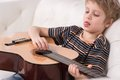 Smiling caucasian boy is playing the acoustic guitar sitting on couch on white background Royalty Free Stock Photos