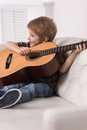 Smiling caucasian boy is playing the acoustic guitar sitting and on couch on white background Stock Photos