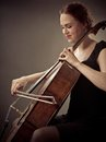 Smiling cellist playing her old cello photo of a beautiful woman an Royalty Free Stock Photo