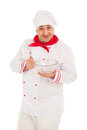 Smiling chef holding whisk and transparent bowl weraing red and white uniform over white background Stock Photography